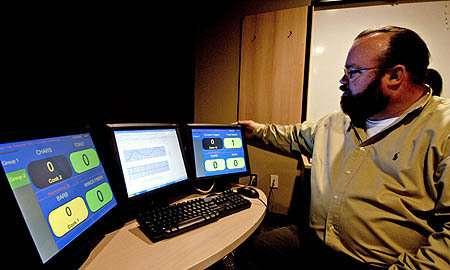"""Kerien Fitzpatrick, le fondateur de la société Hyperactive Technologie, devant un poste de travail """"dirigé"""" par Bob (Crédits : Hyperactive Technologie)"""