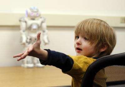 L'autisme est un trouble du développement. Pour mieux atténuer les symptômes, il faut agir le plus tôt possible. Le robot Nao, en arrière-plan, doit pouvoir toucher et sensibiliser les jeunes enfants. © Joe Howell, université Vanderbilt