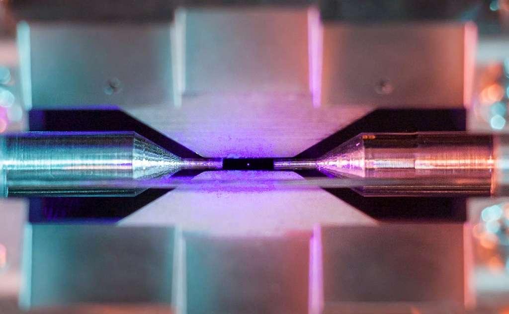 La distance entre les pointes d'aiguille est d'environ deux millimètres. Lorsqu'il est éclairé par un laser de couleur bleue-violette, l'ion de strontium piégé dans l'expérience absorbe et réémet des photons rapidement. Avec un appareil photo ordinaire, une pause longue accumule ces grains de lumière en observant à travers une fenêtre de la chambre à ultra-vide qui abrite le piège à ions. La petite tache colorée qui apparaît alors ne montre bien sûr pas la taille de l'atome mais elle signale spectaculairement sa présence. © David Nadlinger, University of Oxford