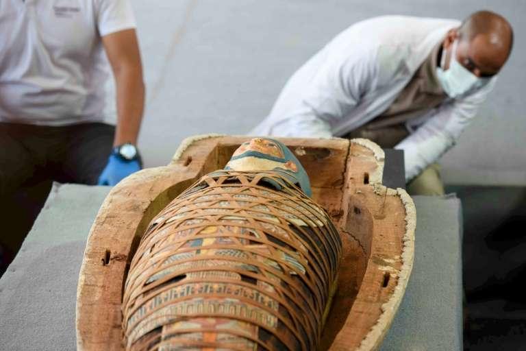 Des archéologues ouvrent un sarcophage découvert à Saqara, lors d'une cérémonie le 14 novembre 2020. © Ahmed Hasan, AFP