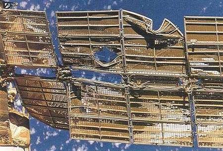 Un aperçu des dégâts occasionnés par la collision de Progress M-34 avec la station Mir le 25 juin 1997. L'accident a déformé les panneaux solaires mais il aurait pu toucher la coque... Crédit Nasa