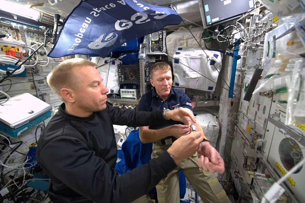 Prise de sang pour l'astronaute européen, de nationalité britannique, Tim Peake (à droite). Elle est réalisée par l'astronaute américain Tim Kopra. © Esa, Nasa