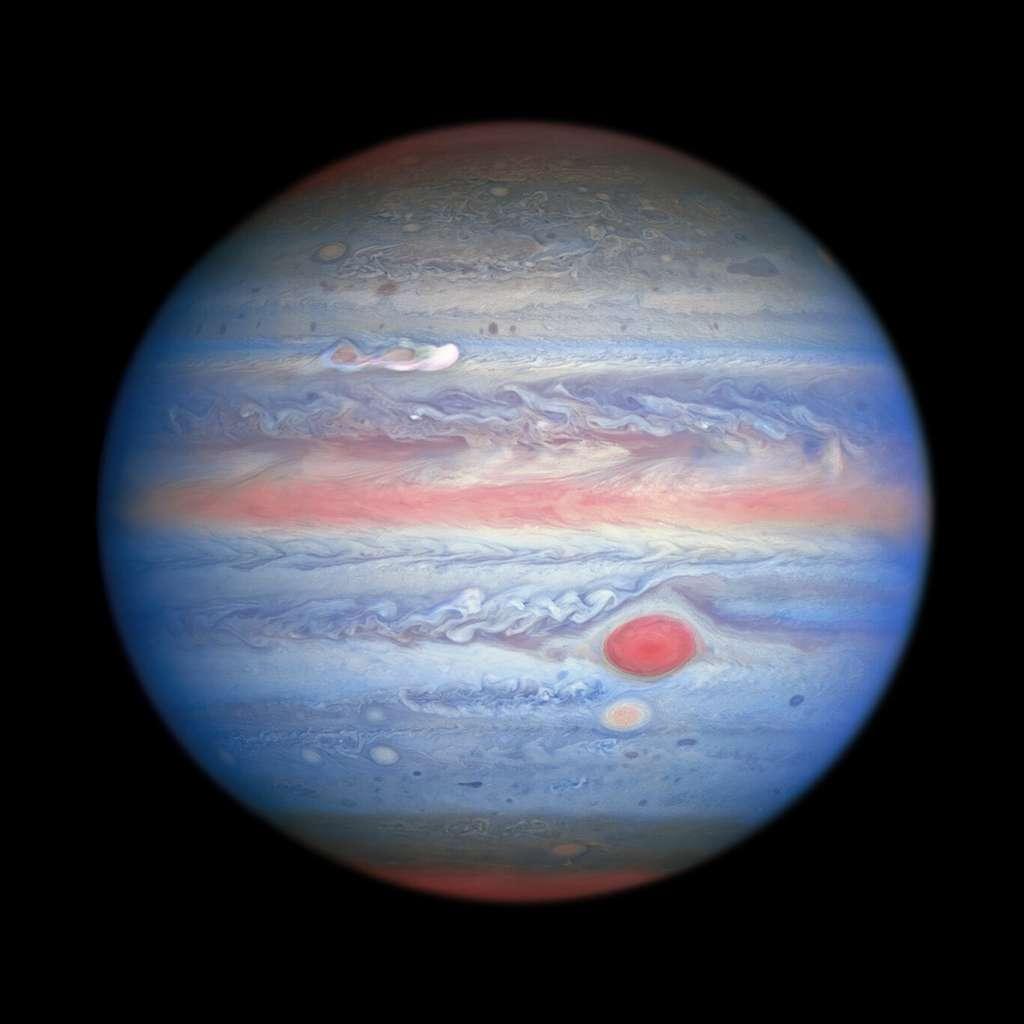 Une observation multi-longueurs d'onde en lumière ultraviolette, visible, proche infrarouge de Jupiter obtenue par le télescope spatial le 25 août 2020. L'imagerie dans le proche infrarouge de Hubble, associée à des vues ultraviolettes, présente un aspect panchromatique unique qui offre des informations sur l'altitude et la distribution de la brume et des particules de la planète. Cela complète les images en lumière visible de Hubble qui montrent des structures nuageuses en constante évolution. Sur cette photo, les parties de l'atmosphère de Jupiter qui se trouvent à une altitude plus élevée, en particulier au-dessus des pôles, semblent rouges en raison des particules atmosphériques absorbant la lumière ultraviolette. Inversement, les zones bleues représentent la lumière ultraviolette réfléchie par la planète. © Nasa, ESA, A. Simon (Goddard Space Flight Center), et M. H. Wong (université de Californie, Berkeley) et l'équipe Opal