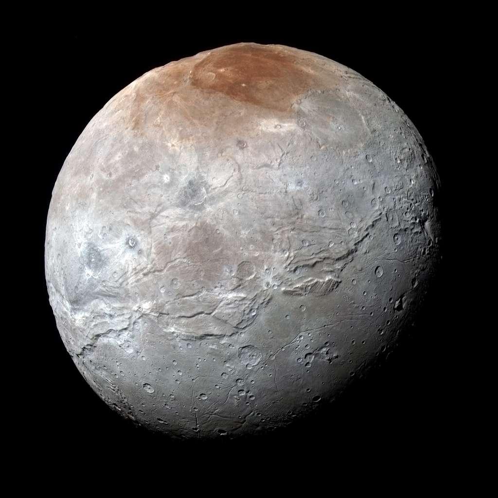 Charon, dans une image réalisée avec le spectromètre imageur MVIC, doté de détecteurs sensibles au bleu, au rouge, à l'infrarouge et aux longueurs d'onde correspondant à la réflexion du méthane. Le relief du satellite de Pluton apparaît varié, avec une grande région lisse et cratérisée au sud et une surface plus tourmentée au nord. Entre les deux, une sorte d'immense vallée mesure un millier de kilomètres de longueur. Et de quoi est faite cette étrange tache rouge? © Nasa, JHUAPL, SwRI