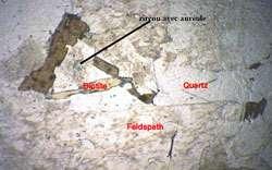 Zircon avec auréole de radioactivité. On voit sur cette image en lumière naturelle, et à faible grossissement, que la désintégration radioactive des éléments du cristal de zircon a des conséquences sur la partie de la roche qui entoure celui-ci. © DR
