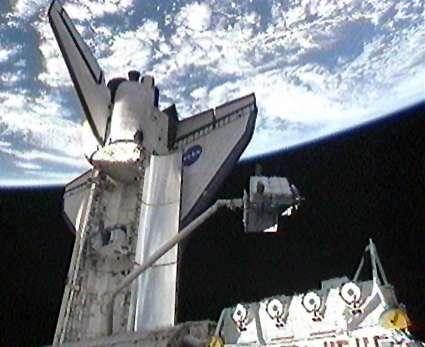 Le bras Canadarm piloté par la Canadienne Julie Payette et l'Américain Timothy Kopra (Nasa) extrait de la navette Endeavour une énorme boîte à outils, l'Integrated Cargo Carrier. © Nasa TV