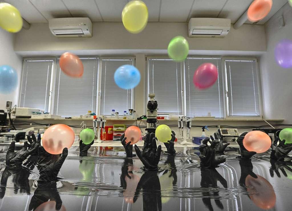 La chimie clic a inspiré les chercheurs pour lier des nanoparticules d'or sur un substrat de carbone. Sur cette installation, les mains gantées représentent les azotures capables d'accrocher les acyles, représentés quant à eux par les ballons multicolores. © IPC PAS, Grzegorz Krzyżewski