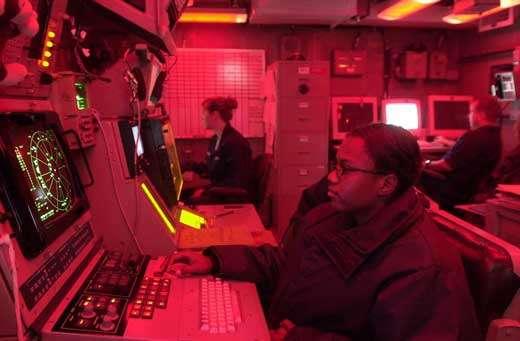 """Toutes les télécommunications transmises par mode analogique (SSB, AM, FM, etc) civiles ou militaires sont très sensibles aux interférences et au bruit et doivent être protégées ou remplacées par des modes numériques beaucoup plus sûrs. Une opératrice aux commandes du système de brouillage SLQ-32 SEEC (Surface Electronics Emission Console) à bord du porte-avion USS Nimitz (CVN 68) dans les eaux du Golfe d'Arabie. Cette console électronique très sophistiquée supporta les soldats de la coalition internationale """"Operation Iraqi Freedom"""" (OFI) qui mis fin au régime de Saddam Hussein en 2003. © Documents U.S.Navy et A.F.Link."""