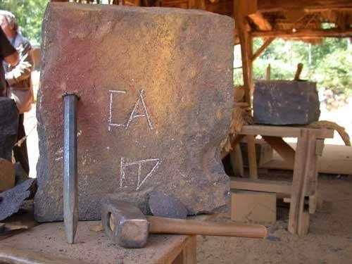 Outils de tailleur de pierres - À gauche : broche et à droite : massette. Sur la pierre est gravée une marque, appelée marque lapidaire. Cette marque est la signature du tailleur de pierre. Sur une pierre (ou un pièce de bois), on peut trouver également d'autres marques : les marques de pose, qui indiquent l'endroit où la pierre doit être posée dans la construction. © Guédelon - Reproduction et utilisation interdites - Tous droits réservés