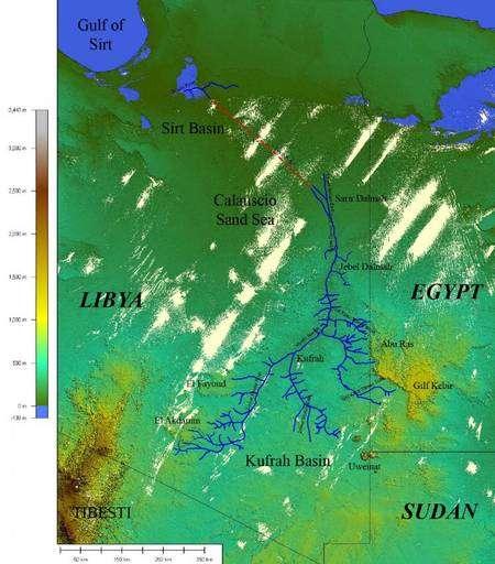Cliquez pour agrandir. Le paléo-fleuve de Kufrah, en bleu, sur un fond topographique SRTM. La ligne rouge pointillée représente le chemin probable vers la mer Méditerrannée sous les dunes du désert libyen. Crédit : OASU Bordeaux (INSU-CNRS, Univ. sciences et technologie Bordeaux)