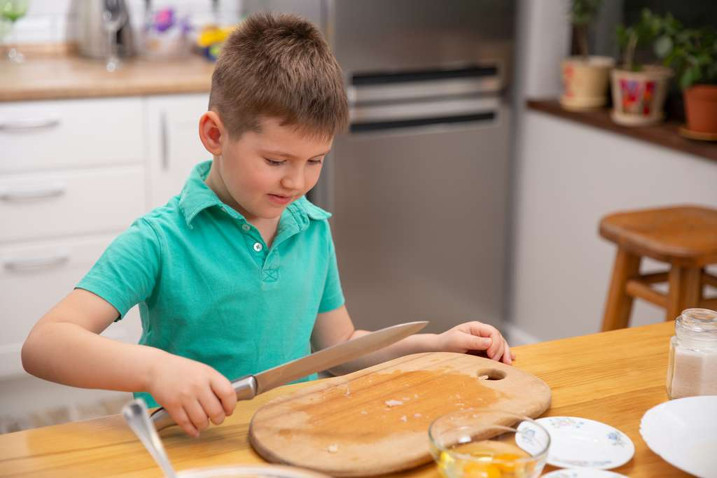 Ne laissez pas votre enfant manipuler des couteaux tranchants. Confiez-lui des tâches moins dangereuses ! © Volodymyr Shcerbak, Adobe Stock