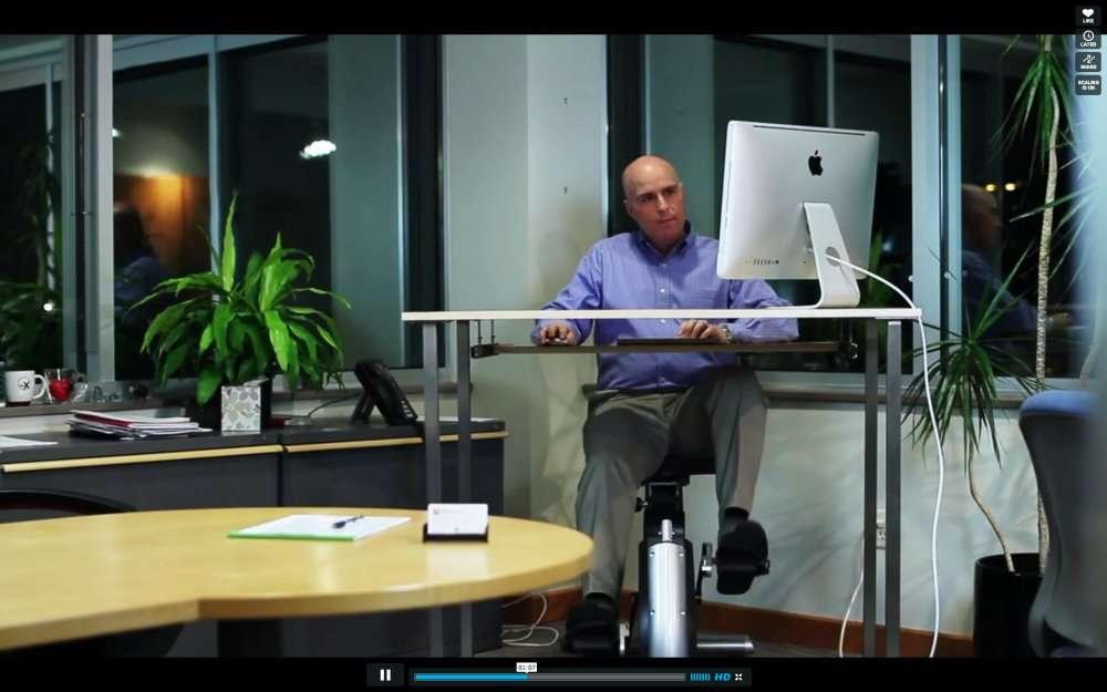 Sous le bureau, un vélo. C'est l'idée d'un scientifique spécialiste du sport. On voit ici la capture d'une vidéo montrant le principe de l'Active Desk (« bureau actif »). © 2013 Vimeo, LLC, DR