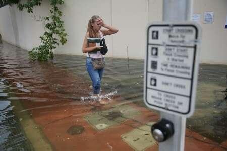 Une jeune femme marche dans une rue de Miami, inondée par une marée haute saisonnière, le 29 septembre 2015 au sud-est des États-Unis. © Joe Raedle, Getty images North America, AFP, Archives