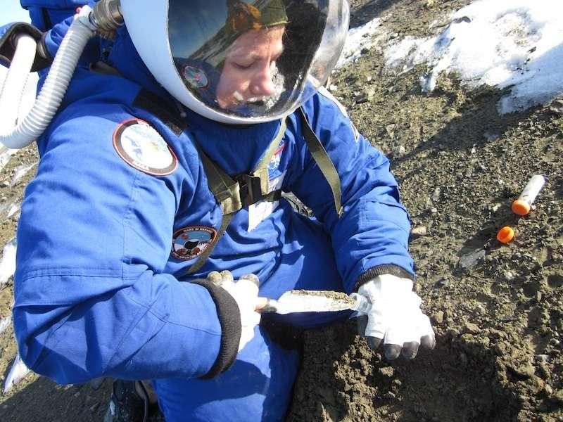 Margarita Marinova en train de récolter des échantillons du sol de l'île de Marambio, au large de la péninsule de Palmer en Antarctique, qu'elle introduit avec une truelle dans un tube Falcon. © Jon Rask