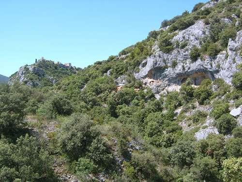 Photo 3 : Vue générale du site des Auzières, avec le village de Méthamis en arrière-plan. On aperçoit au milieu de l'image la bâche bleue tendue au dessus de la fouille. © Mathieu Mazières Reproduction et utilisation interdites