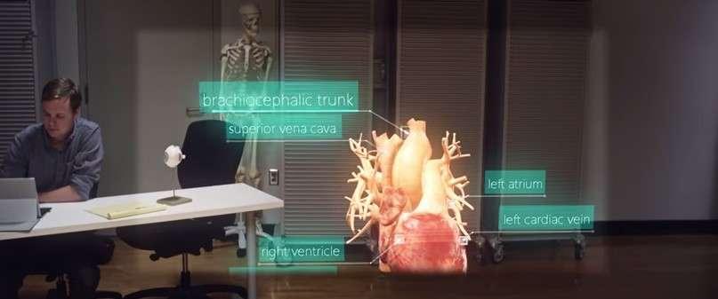 Sur cette capture réalisée dans la vidéo YouTube de démonstration des HoloLens, on constate que le champ de vision effectif des lunettes se limite au cadre rectangulaire éclairé dans la partie centrale de l'image. La moitié inférieure du cœur représenté en réalité augmentée est tronquée, de même que la tête du squelette en arrière-plan et la personne qui se tient à son bureau. © Microsoft