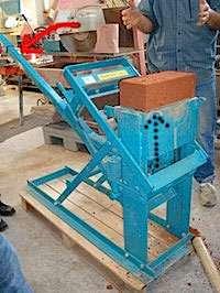 Brique de terre crue compressée réalisée à l'aide d'une presse manuelle. Le mécanisme est pourvu d'un grand bras de levier qui démultiplie la force de pressage.© lamaisondurable.com