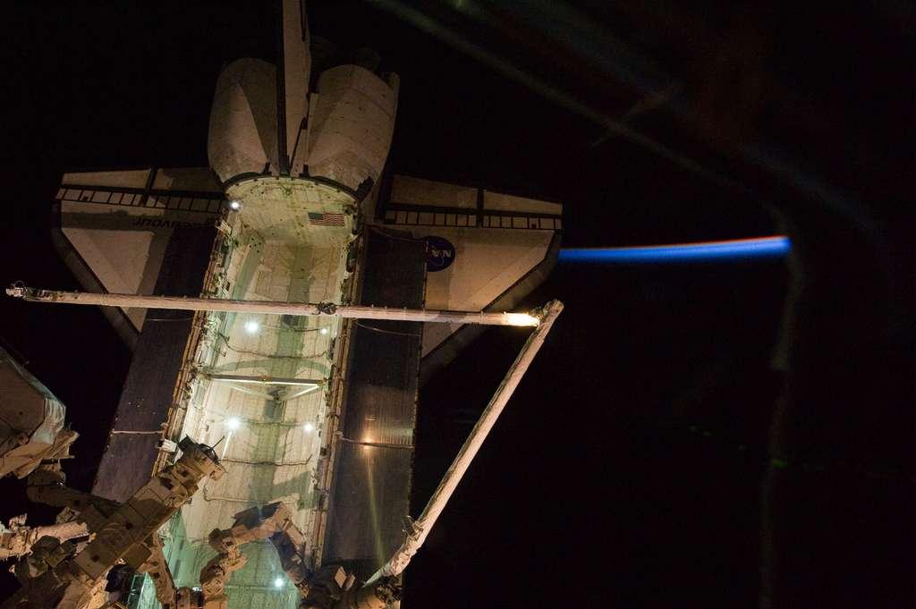 Depuis la perte de la navette Columbia en février 2003, en raison de la fragilisation du bord d'attaque de l'aile gauche, chaque navette fait l'objet d'inspections en orbite qui peuvent être réalisées soit par l'équipage de l'ISS, soit par la perche d'inspection OBSS (à l'image, au bout du Canardarm), ou des deux. © Nasa