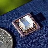 Figure 1. L'instrument, constitué d'un circuit et surmonté d'un cube transparent transmettant la lumière. A gauche, la pièce de monnaie, un quarter mesurant 24,26 millimètres de diamètre, donne l'échelle. © National Academy of Sciences, Pnas (2008)