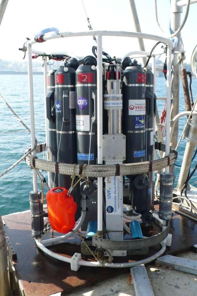 La rosette, mise au point au laboratoire de Villefranche-sur-mer, par Marc Picheral. Elle porte dix bouteilles de prélèvement et, visible au premier plan, l'UVP, Underwater Vision Profiler. Cette caméra, dirigée vers le bas, filme tout au long de la descente la tranche d'eau éclairée par deux projecteurs horizontaux. Un ordinateur capte les images et compte les organismes en temps réel, entre 500 microns et quelques centimètres. Des structures fragiles sont ainsi repérées et identifiées, alors qu'elles seraient écrasées dans un filet à plancton. © Jean-Luc Goudet/Futura-Sciences