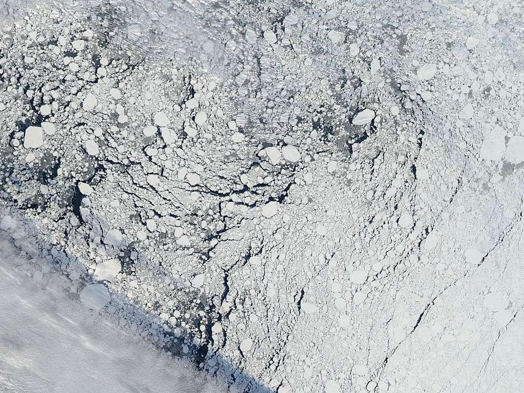 La banquise arctique au nord de l'Alaska, captée par l'instrument Modis sur le satellite Aqua de la Nasa le 13 septembre 2013. On peut observer un front de nuages dans le coin inférieur gauche, et les zones sombres indiquent les régions d'eau libre entre les formations de glace de mer. © Nasa Worldview