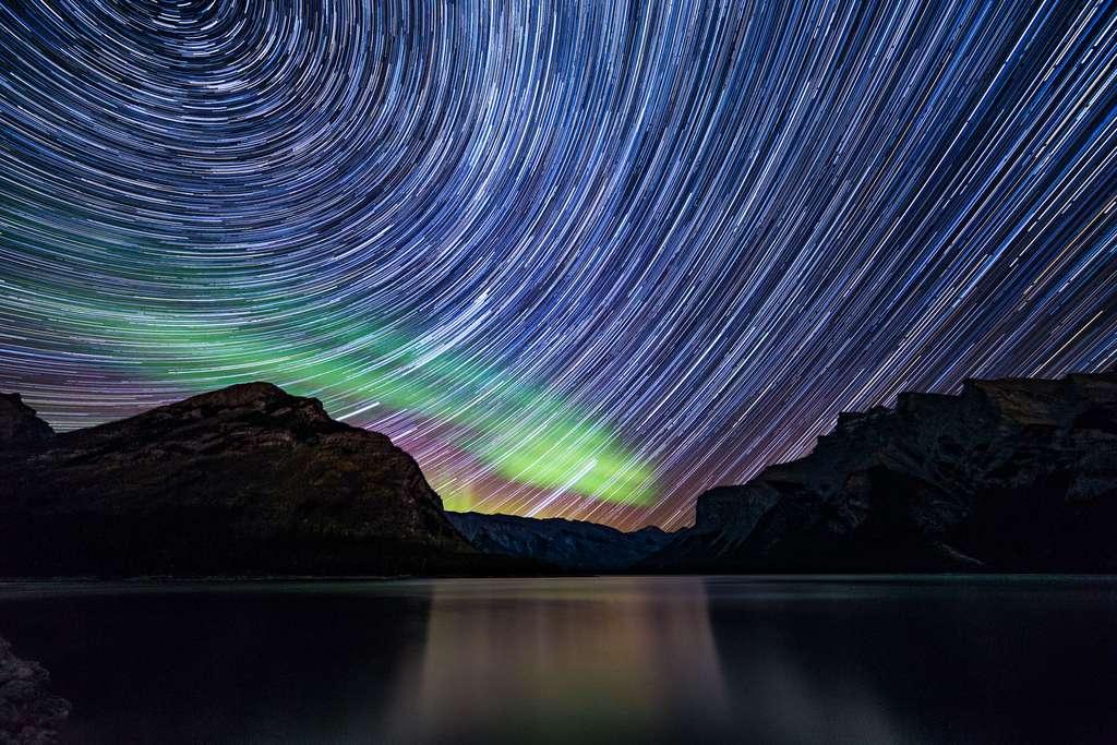 Les étoiles les plus brillantes du ciel boréal laissent un filet lumineux accompagnant la rotation de la Terre. Une aurore s'est invitée dans ce décor naturel. © Deepanshu Arora