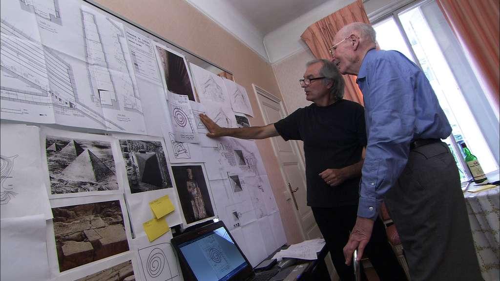 L'architecte Jean-Pierre Houdin (en arrière-plan) proposant une autre forme de rampe. À ses côtés, son père, Henri Houdin, à l'origine de la première forme imaginée de la rampe interne, une spirale. © Gedeon Programmes