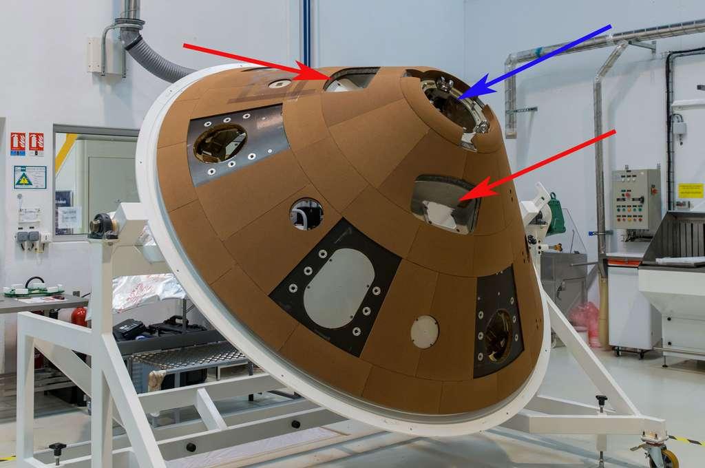 Le cône arrière du bouclier thermique de la capsule Schiaparelli avant sa livraison à Thales Alenia Space. Il est ici vu dans une des salles blanches du site de Saint-Médard-en-Jalles (près de Bordeaux) d'Airbus Espace. Les flèches rouges indiquent deux des trois emplacements où sera accroché le bouclier à l'orbiteur et la bleue l'emplacement du parachute. © Airbus Defence & Space, A. Gilbert