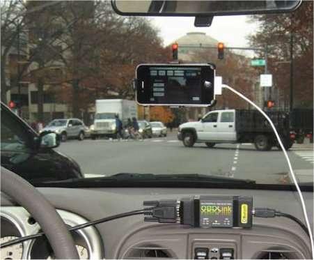 Un iPhone installé sur le parebrise détecte les feux tricolores et envoie l'information à tous les autres appareils du réseau. En même temps, le smartphone prédit, grâce aux informations reçues des autres téléphones, le moment du passage au vert et calcule la vitesse pour atteindre le feu à cet instant. L'autre appareil fixé sur le tableau de bord mesure la consommation pour les besoins de l'expérience. On note que le dispositif ne fonctionne qu'avec des feux situés au-dessus de la route, une position systématique aux États-Unis. Les feux situés sur le trottoir, comme c'est souvent le cas en France, ne seront pas détectés par le smartphone. © Emmanouil Koukoumidis, Li-Shiuan Peh, Margaret Martonosi