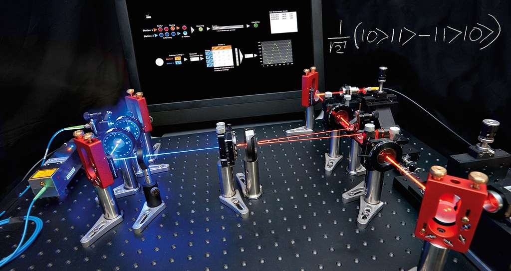 Un dispositif illustrant le principe de la production de paires de photons intriqués. Un laser (bleu) passe à travers un cristal où un phénomène d'optique non linéaire produit deux faisceaux (en rouge) avec des paires de photons en sortie. L'état quantique de ces paires est inscrit sur un tableau noir. © IQOQI Vienna, Austrian Academy of Sciences