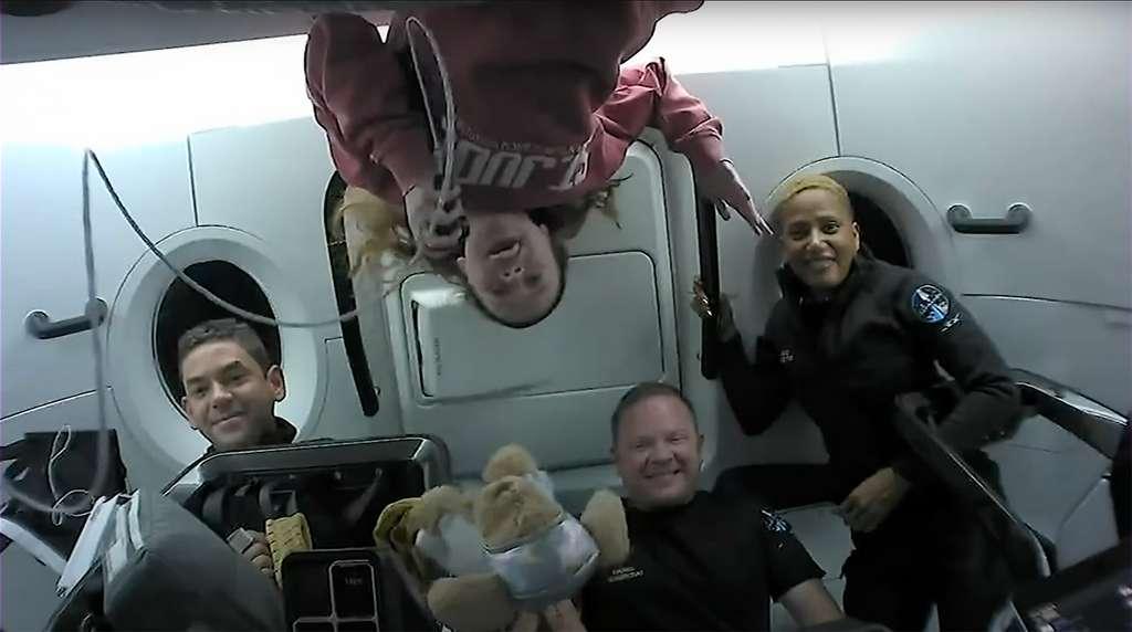 Les « spatiotouristes » d'Inspiration4 à bord du Crew Dragon de SpaceX. Cet équipage est composé du commandant Jared Isaacman (à gauche), qui finance la mission, du pilote Siam Proctor (à droite), de Haylel Arceneaux (la tête à l'envers), responsable médicale, et du spécialiste de mission Christopher Sembroski. © SpaceX