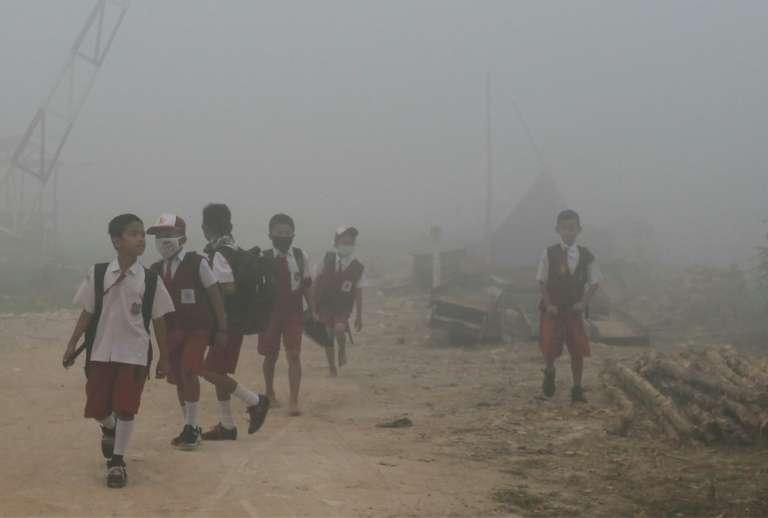 Des enfants indonésiens marchent vers leur école dans l'air pollué par de gigantesques incendies de forêt à Palembang, dans l'île de Sumatra, en octobre 2019. © Abdul Qodir, AFP