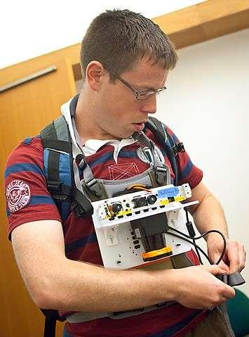 Le système de cartographie en temps réel portable se porte sur la poitrine. On distingue dans la partie supérieure les capteurs du dispositif Kinect et en dessous le télémètre laser en position verticale. © MIT/CSAIL