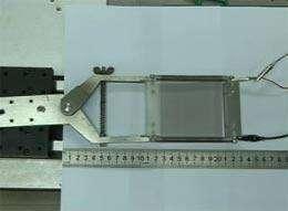 Cliquez sur l'image pour ouvrir la vidéo (format quicktime). Le film de nanotubes (le carré gris au centre de l'image) est élastique. On distingue, à droite, les fiches électriques. Il peut être allongé sans que la musique diffusée soit altérée. © Jiang Kaili et al., ACS Nano Letters