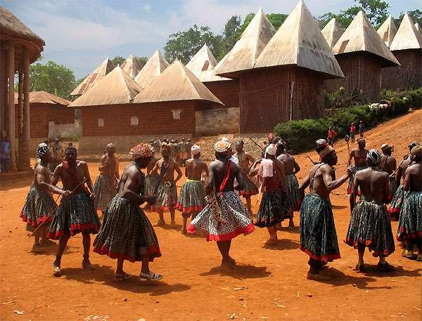 Danse traditionnelle dans la cour royale du palais de Bamendjou. Sur l'extrême gauche, un aperçu de la grande case, et en arrière-plan, le quartier des femmes du chef. © Olivier Testa