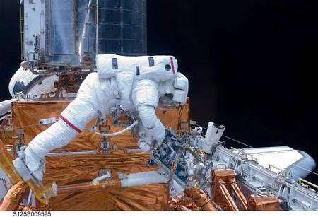 John Grunsfeld saisit le nouveau capteur de pointage précis (FGS) dans la soute d'Atlantis. Cliquer pour agrandir. Crédit Nasa