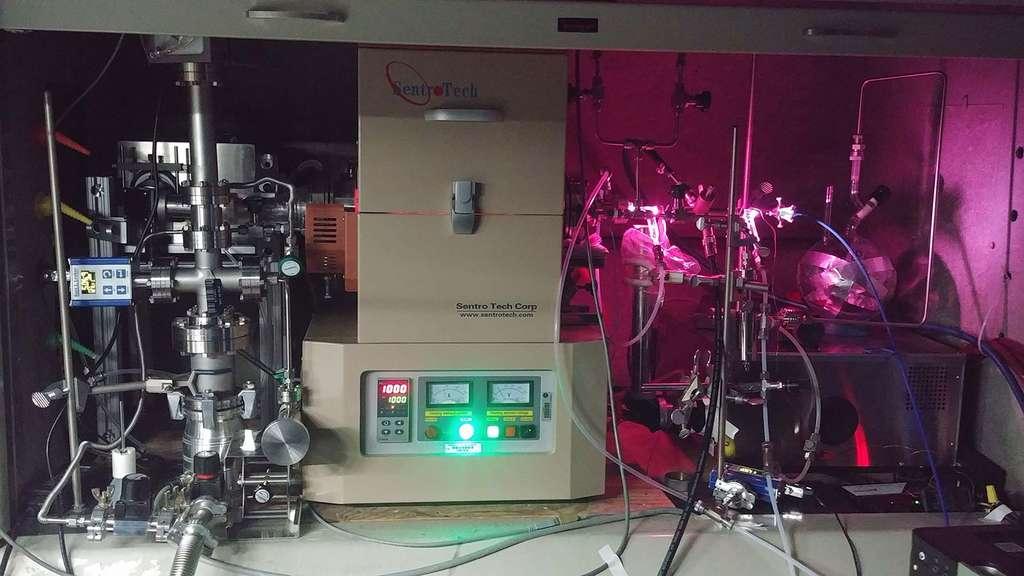 Les scientifiques du JPL ont utilisé un « four » (au centre) pour chauffer un mélange d'hydrogène et de monoxyde de carbone et le soumettre à un rayonnement ultraviolet généré par une lampe à décharge. La lampe émet une lumière visible (la lueur rose) et une lumière UV, qui pénètrent dans le réservoir de gaz à l'intérieur du four par une fenêtre du côté droit. © Nasa/JPL-Caltech