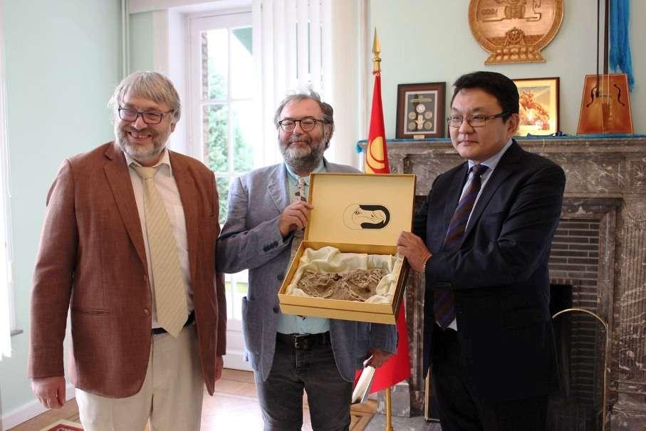 De gauche à droite, Pascal Godefroit et François Escuillié, récompensés lors d'une cérémonie par l'ambassadeur de Mongolie en Belgique. Le fossile montré n'est pas celui de Halszkaraptor escuilliei. © François Escuillié