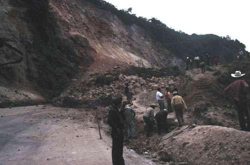 Un important éboulement (« derrumbe ») au Guatemala dans la province de Quetzaltenango le 7 décembre 1978. Une voiture avec ses trois occupants a été ensevelie. Les voyageurs quittent les cars pour franchir l'obstacle à pied et reprendre les véhicules bloqués de l'autre côté. © J.-M. Bardintzeff