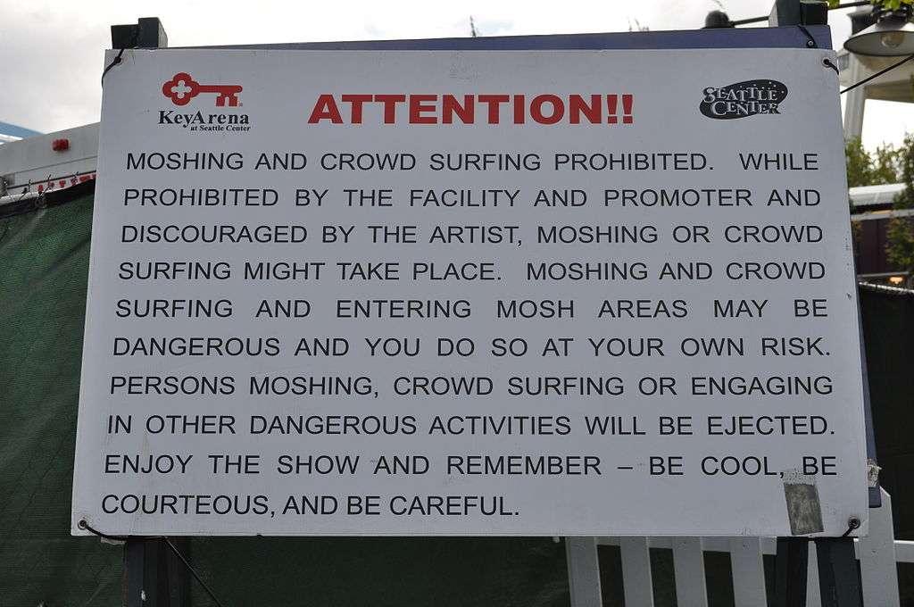 Outre le headbanging, d'autres pratiques de festivaliers peuvent être dangereuses pour leur santé ou celle d'autrui. Ici, un panneau en bordure de scène rappelle aux fans de musique qu'il est interdit de danser en se bousculant les uns les autres (moshing, pogoter en français) ou de se jeter dans la foule depuis la scène (crowd surfing, slammer). © Joe Mabel, Wikimedia Commons, cc by sa 3.0