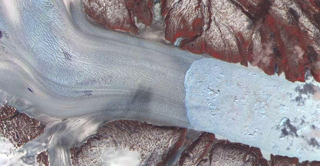 Au-delà de la hausse des températures, les suies des feux de forêt et la formation de nuages peuvent avoir un impact important sur la fonte des glaciers du Groenland – ici le glacier Helheim vu par satellite en juillet 2003. Les modèles climatiques peinent encore à intégrer ces paramètres. © Nasa