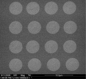 Seize lentilles constituées de simples cercles concentriques gravés sur une plaque d'argent. Sous l'effet d'un rayonnement ultraviolet, elles émettent des ondes de longueurs d'onde plus courtes au niveau du trou central. (Cliquez pour agrandir.) © Xiang Zhang Lab/UC Berkeley