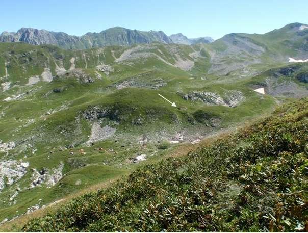 Le gouffre de Krubera-Voronya, dont l'entrée est indiquée par la flèche blanche, se situe dans le massif de l'Arabika au sein du Caucase occidental. Les points bas de la cavité sont également accessibles par deux autres entrées : le gouffre Kuybyshev et l'abîme Heinrich. © Sendra et Reboleira 2012, International Journal of Speleology