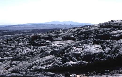 Des coulées à surface plissée (cordée ; de type « pahoehoe ») tapissent le plancher de la caldeira de l'Erta Ale. On voit, à l'arrière-plan, le volcan Hayli Gubbi (521 m), situé dans l'axe du rift (la vue est vers le sud). © J.-M. Bardintzeff, reproduction et utilisation interdites