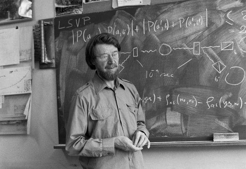 John Bell devant le tableau noir dans son bureau au Cern. On peut y voir tout en haut la fameuse inégalité qu'il a démontrée en 1964, au-dessus d'un schéma montrant le principe de l'expérience réalisée en 1982 avec des paires de photons polarisés par Alain Aspect et ses collègues. © Cern