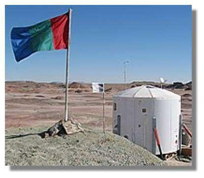 L'habitat simulé implanté par la Mars Society dans le désert de l'Utah. Au premier plan, le « drapeau de Mars », aux couleurs des phases de la terraformation… Crédits : TMS