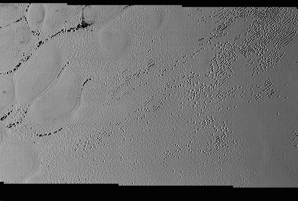 Cette image très détaillée prise avec Lorri montre une multitude de trous de plusieurs centaines de mètres de large entre les cellules de glace au sein de la plaine Spoutnik. Certains semblent moins profonds et beaucoup ont fusionné. La largeur de ce paysage photographié le 14 juillet est de 210 km. © Nasa, JHUAPL, SwRI