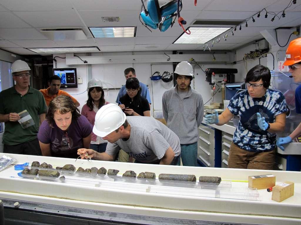 Beth Orcutt (t-shirt mauve) et Wolfgang Bach (université de Brême, Allemagne) examinent un morceau de croûte océanique remonté à bord du navire océanographique JOIDES Resolution. © Jennifer T. Magnusson