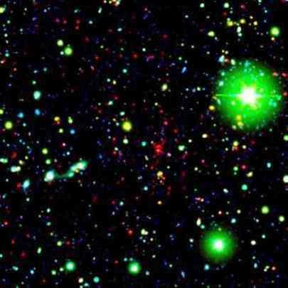 Spitzer observant un amas galactique, situé à 9.09 milliards d'années-lumière de la Terre. Dans cette image composite en fausses couleurs, les galaxies faisant partie de l'amas sont visibles sous la forme de points rouges. Les tâches vertes sont, quant à elles, des étoiles de la Voie Lactée, et les points bleus des galaxies pâles (Crédits : NASA/JPL-Caltech/UCDavis/Lawrence Livermore National Laboratory)