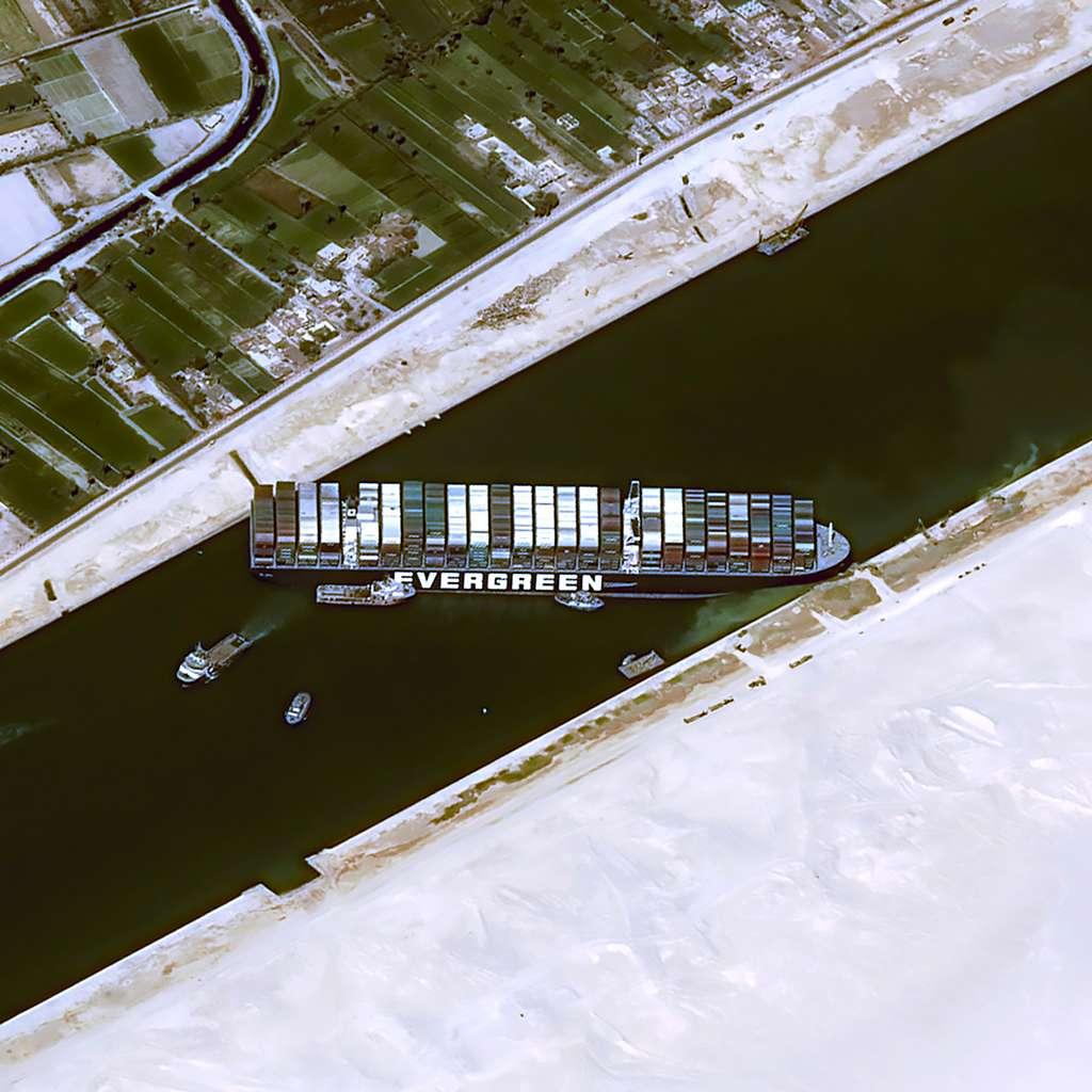 Cette image à très haute résolution du satellite Pléiades montre le porte-conteneurs Ever Given, affrété par Evergreen, échoué et bloquant le canal de Suez. Il est entouré de remorqueurs et de dragueurs qui tentent tant bien que mal de le dégager. Cette image Pléiades a été acquise depuis une altitude de 694 kilomètres avec une résolution de 70 centimètres et ré-échantillonnée à 50 centimètres. Tous les détails chiffrés sur la fauchée et les longueurs d'onde sont dans le visible et le proche infrarouge. Elle a été acquise jeudi matin, à 09:43:33, heure locale, avec un angle de 49°, ce qui permet notamment d'avoir le côté du bateau aussi clairement visible. © Cnes 2021, Distribution Airbus DS